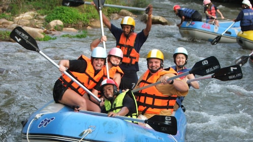 whitewater rafters posing with paddles in Phuket