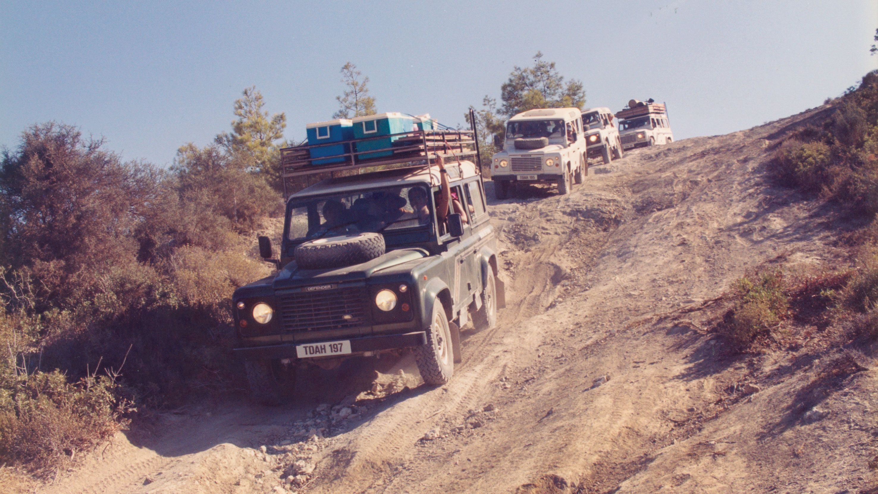 Jeeps carrying gear down steep dusty road in Cyprus