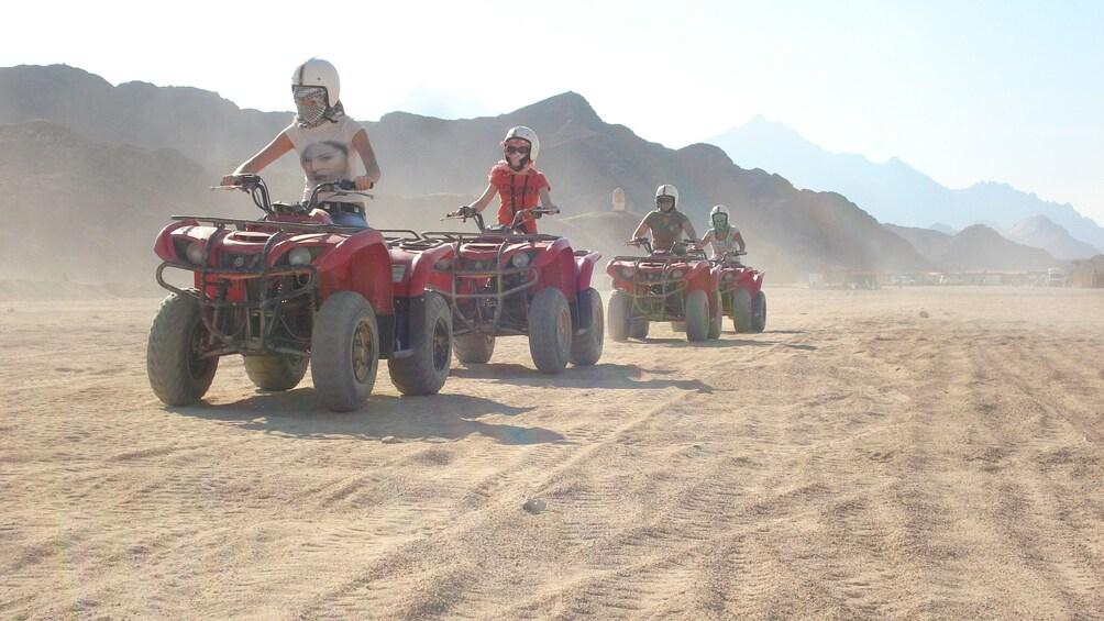 quad bikers ride in a single file line in Sharm el Sheikh