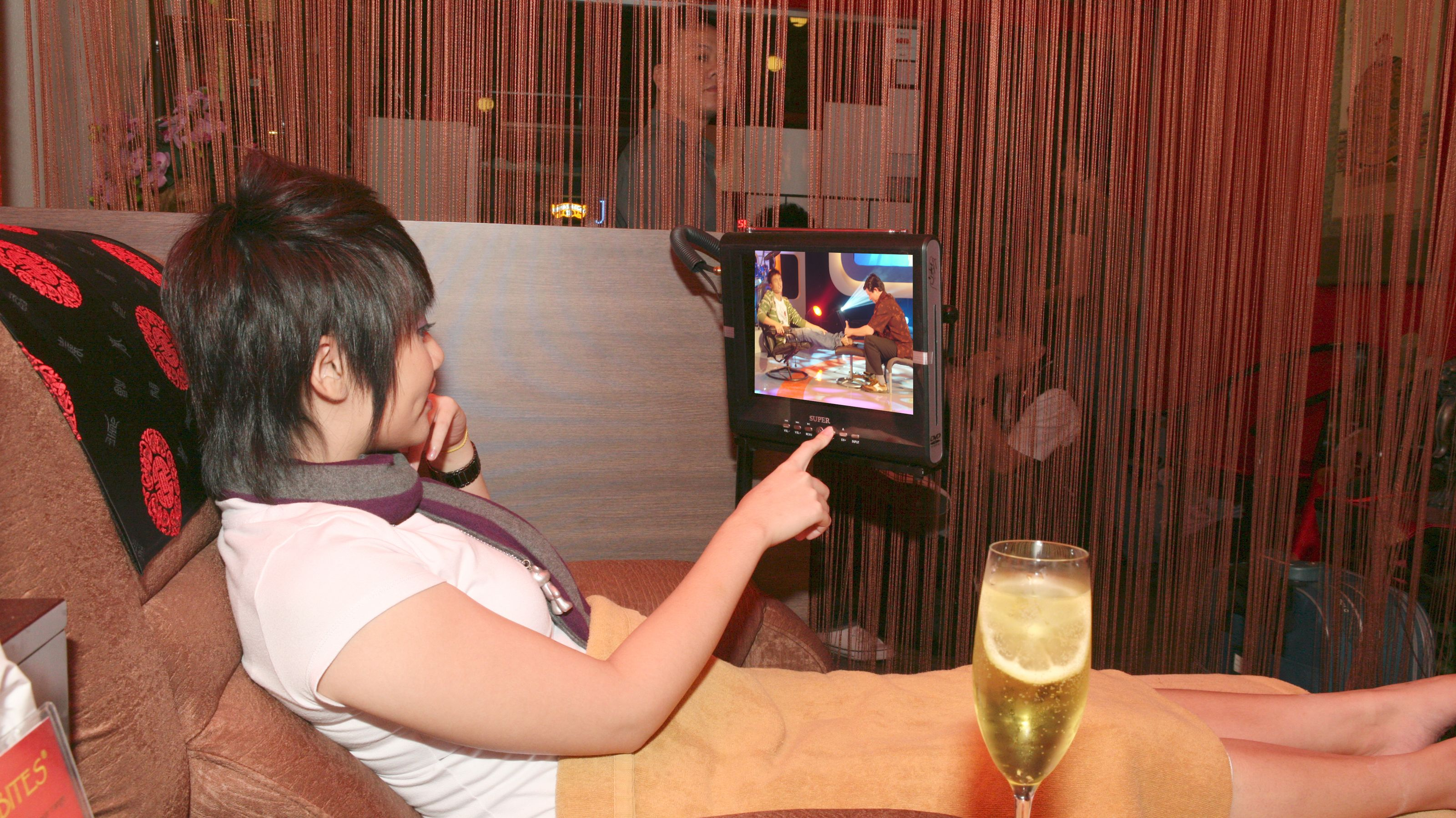 Woman adjusts television at spa in Singapore