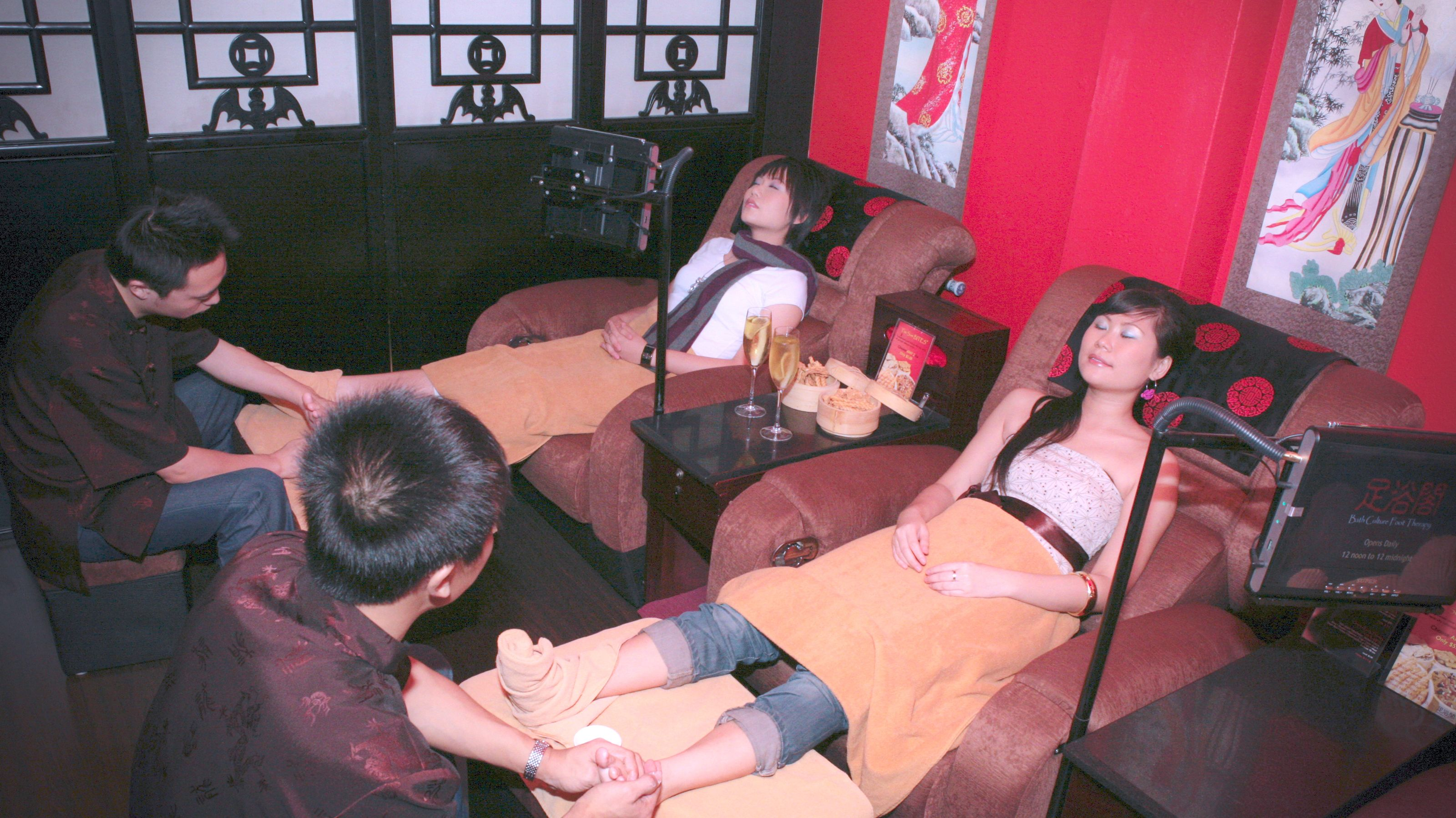 Women relaxing while men tend to their feet in Singapore