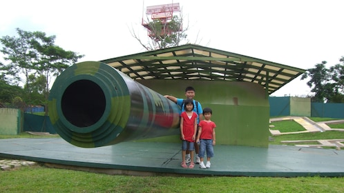 Kids posing next to huge war barrel in singapore