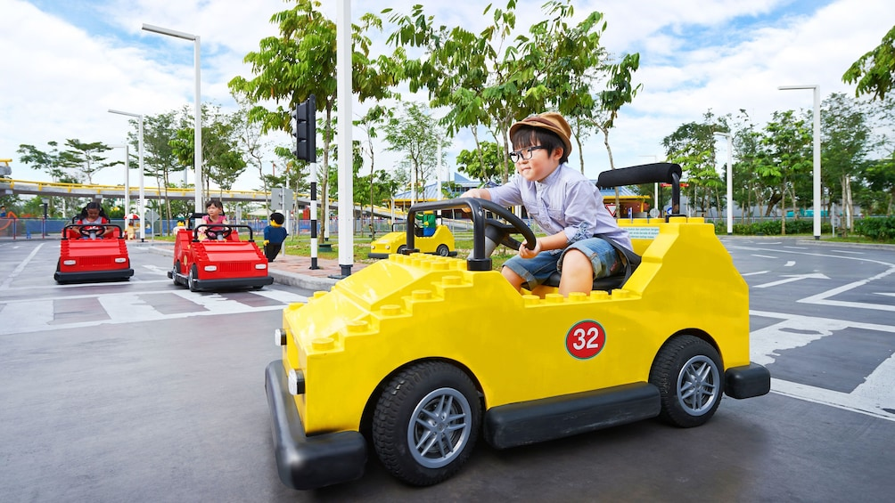 Show item 10 of 10. Kids driving lego cars in Legoland in Singapore