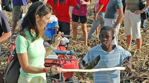 Local child splitting sugar cane in La Romana
