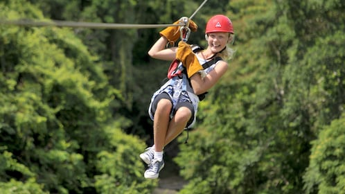 Girl in gear zip lining in La Romana