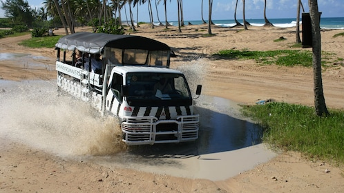 Passenger carrier driving through a puddle of mud in La Romana