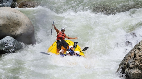 Man in back of yellow raft in the rapids of the Yaque del Norte River