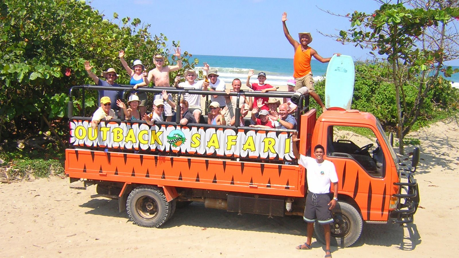 Group picture of activity-goers waving from open-air bus on the beach