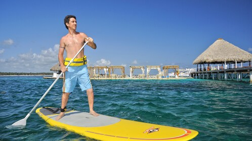 man standing on paddle board in Santo Domingo