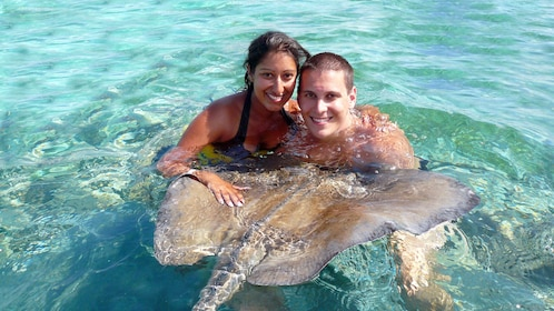 man and woman in water with sting ray in Santo Domingo