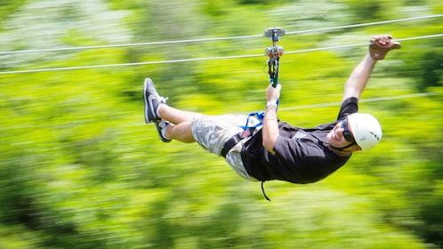 man riding zip line through forest in Santo Domingo
