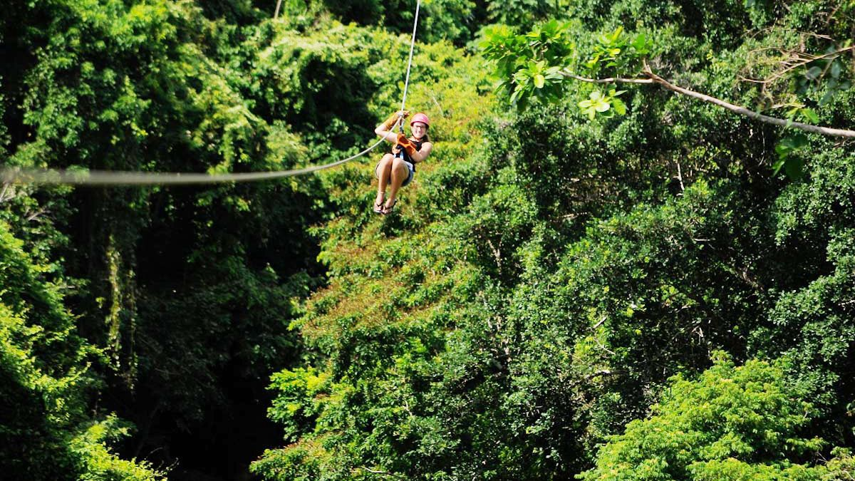 woman riding zip line through forest in Santo Domingo