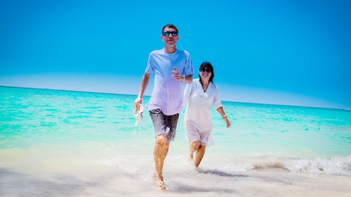 man and woman walking on Juanillo Beach in Punta Cana