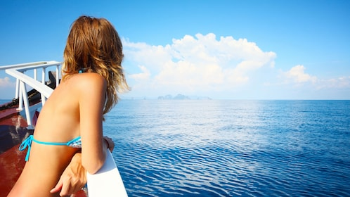 Woman looks out over the bow of a catamaran onto the blue ocean