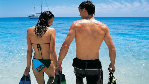 Couple in Bathing suits and snorkeling gear enter the water