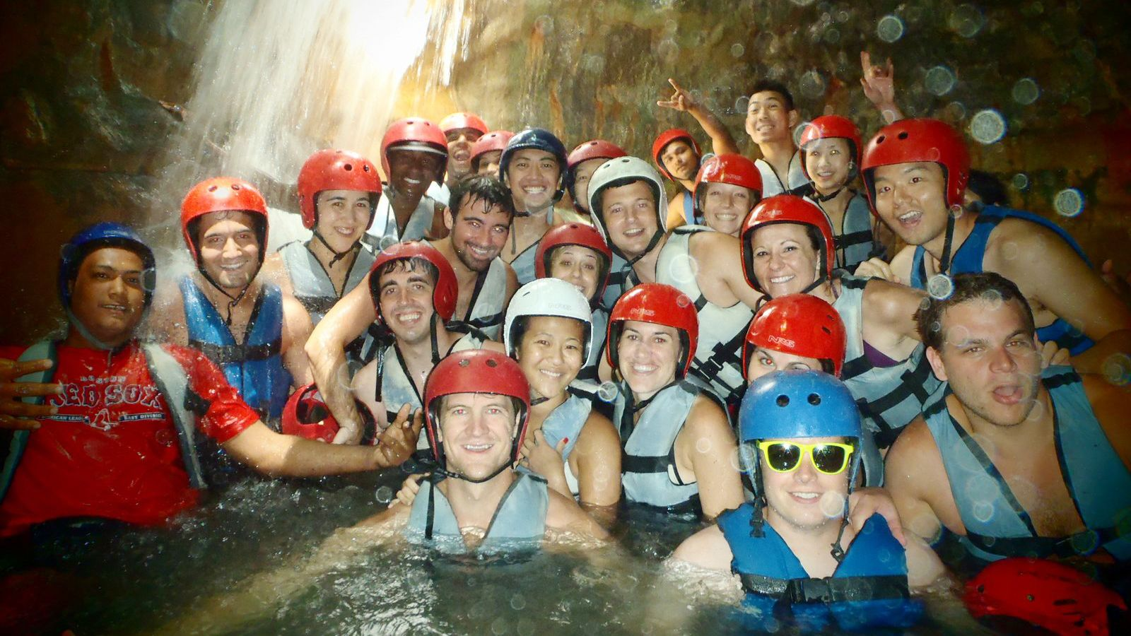 Large group wearing red helmets gathered for a photo in the water