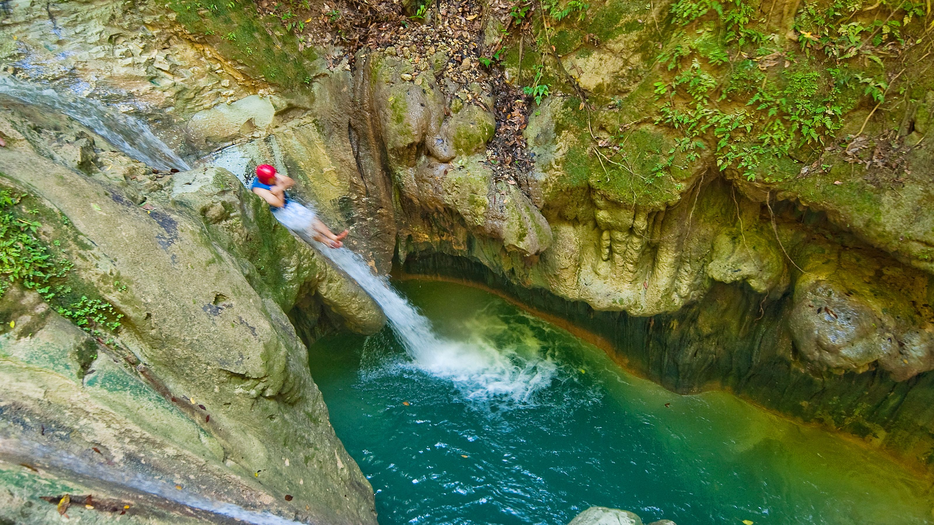 High angle view of person sliding down natural slide into pool of water