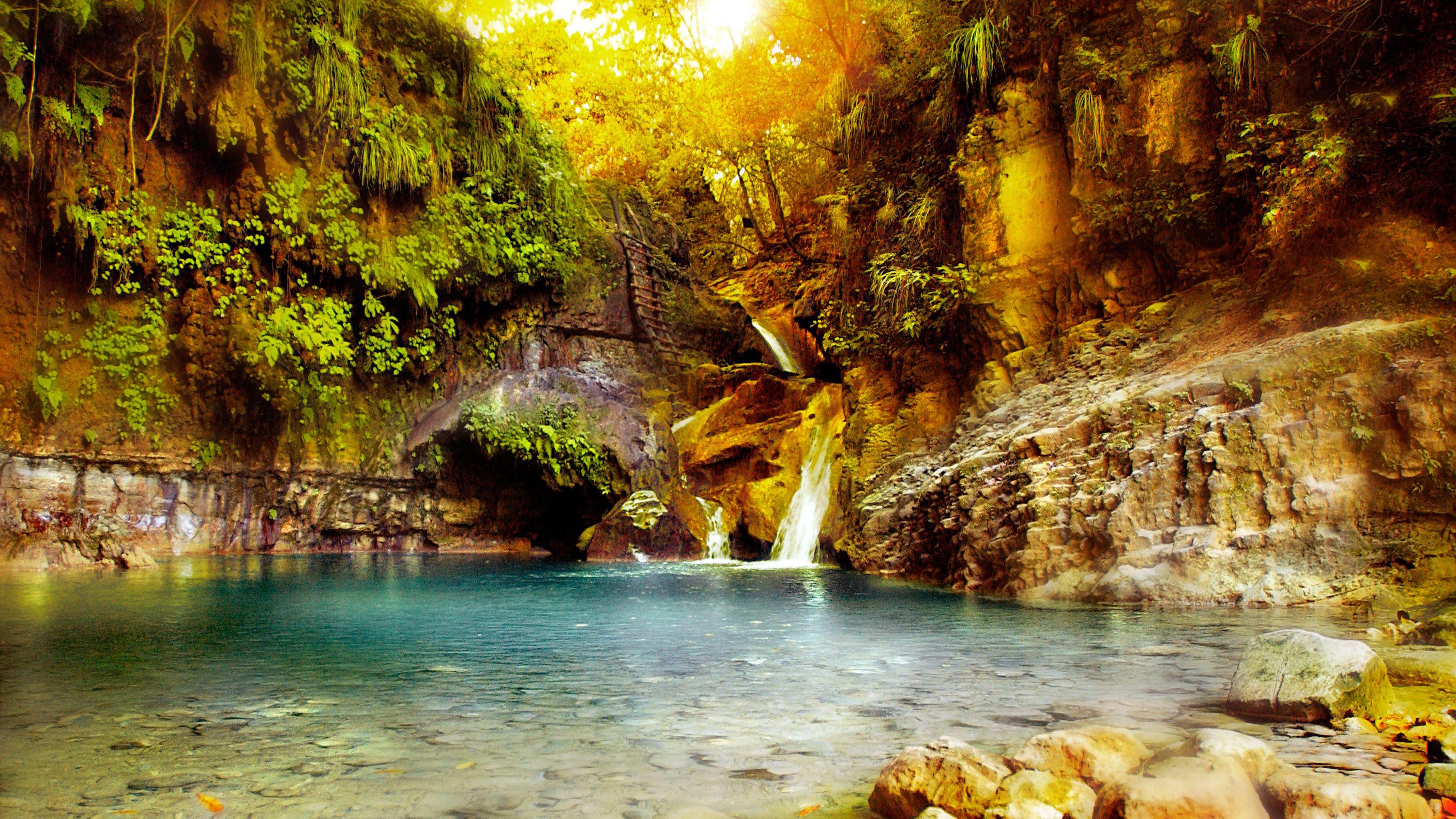 Waterfall into sun splashed clear pool