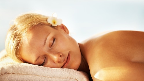 Woman with jasmine flower relaxing her head on a towel pillow