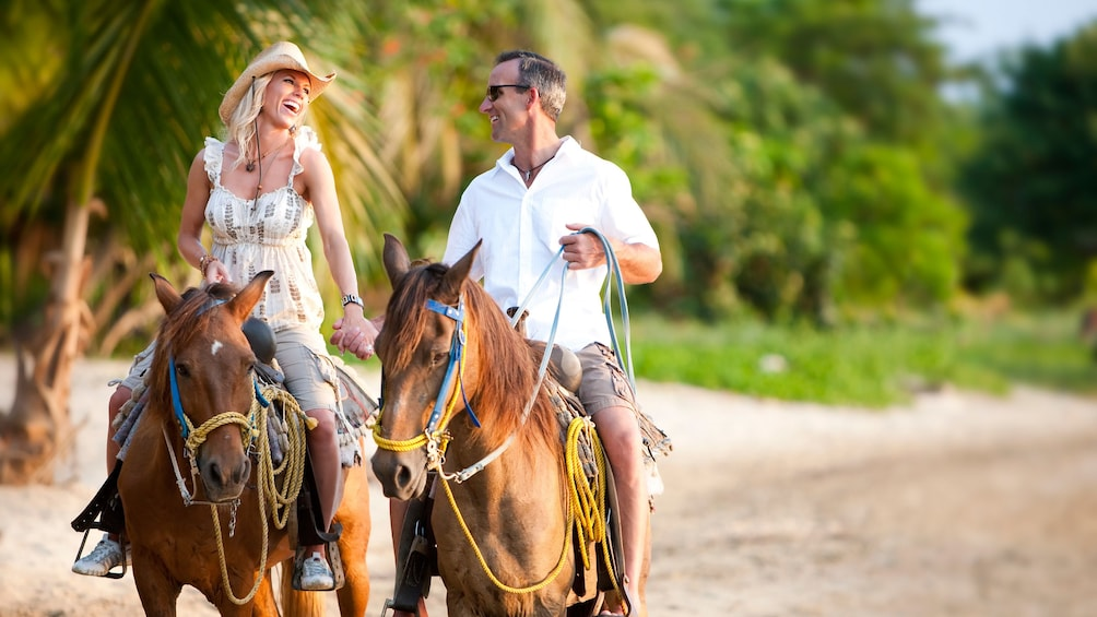 Show item 2 of 5. Couple holding hands and riding horses on the beach