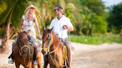 Couple holding hands and riding horses on the beach