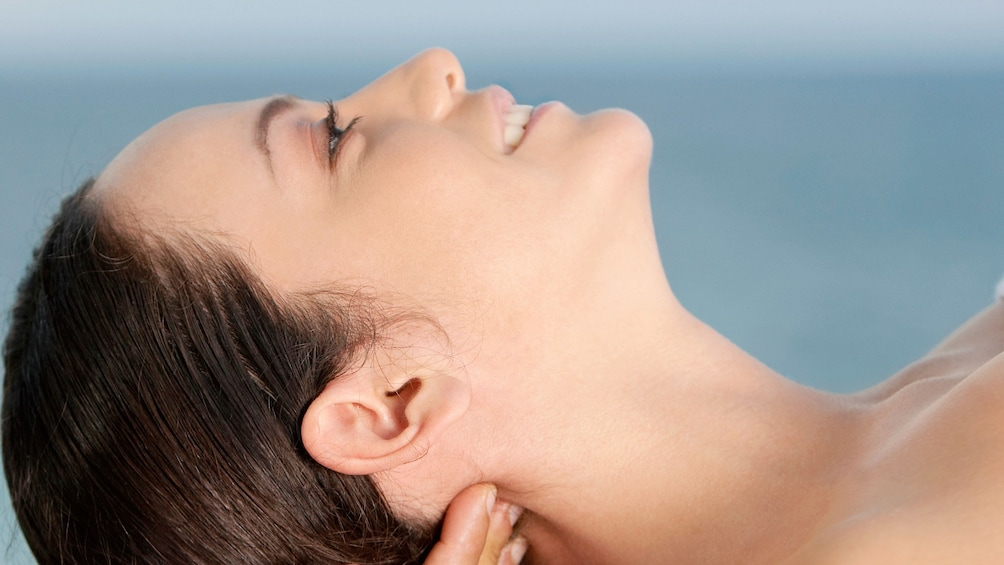 Show item 5 of 5. Smiling woman getting a neck message at Jasmine Spa