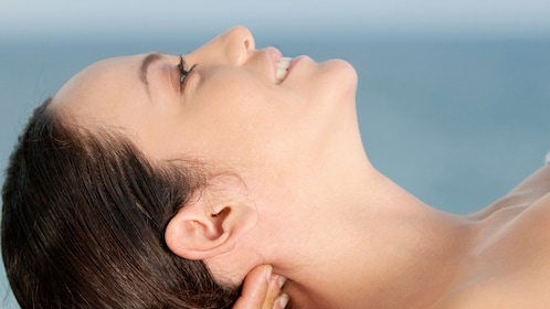 Smiling woman getting a neck message at Jasmine Spa