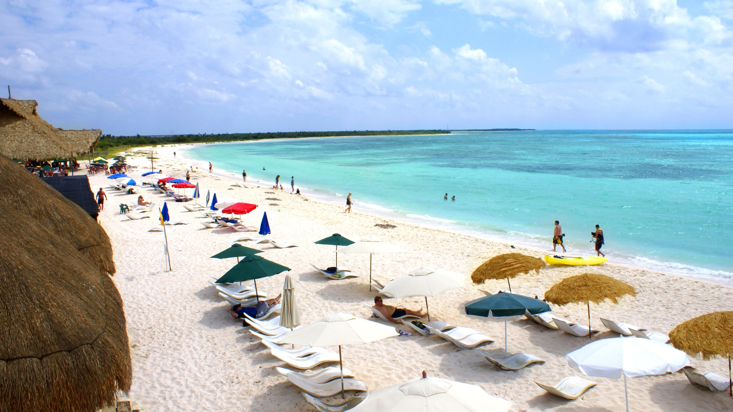 Umbrellas and beach goers on a sandy beach in Riviera Maya