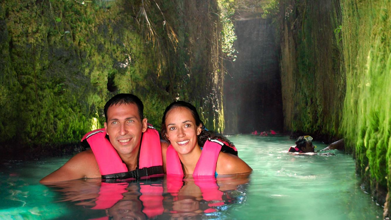 Swimming couple in an underground river at Xcaret Park in Riviera Maya