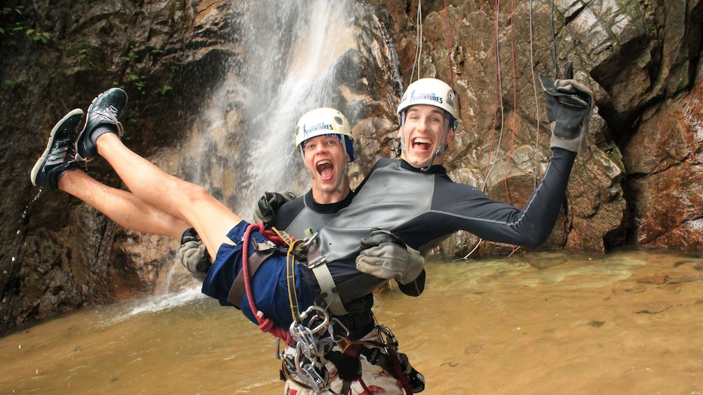 Friends celebrate a successful repel down a majestic waterfall near Boca de Tomatlan and Puerto Vallarta