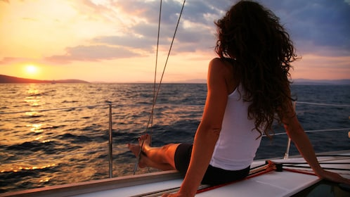 Woman enjoying the sunset from the sailboat