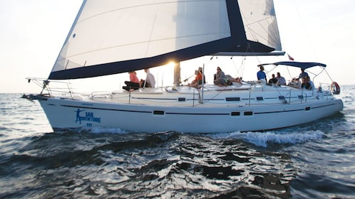 Guests enjoy clear skies from the vantage of a luxury sailboat as the sun sets