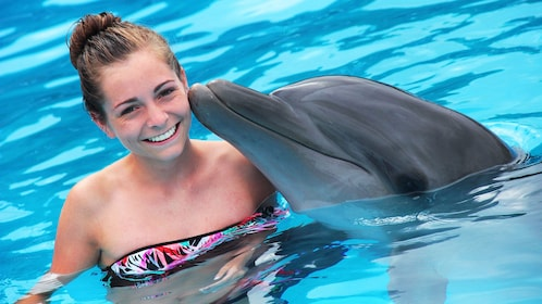 Dolphin kissing a young woman