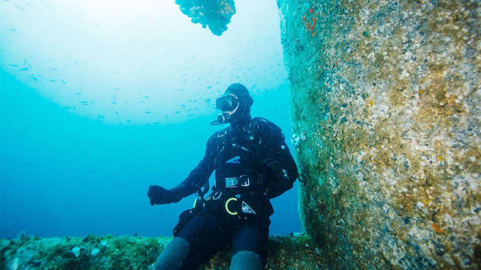 scuba diver sitting on underwater ruins