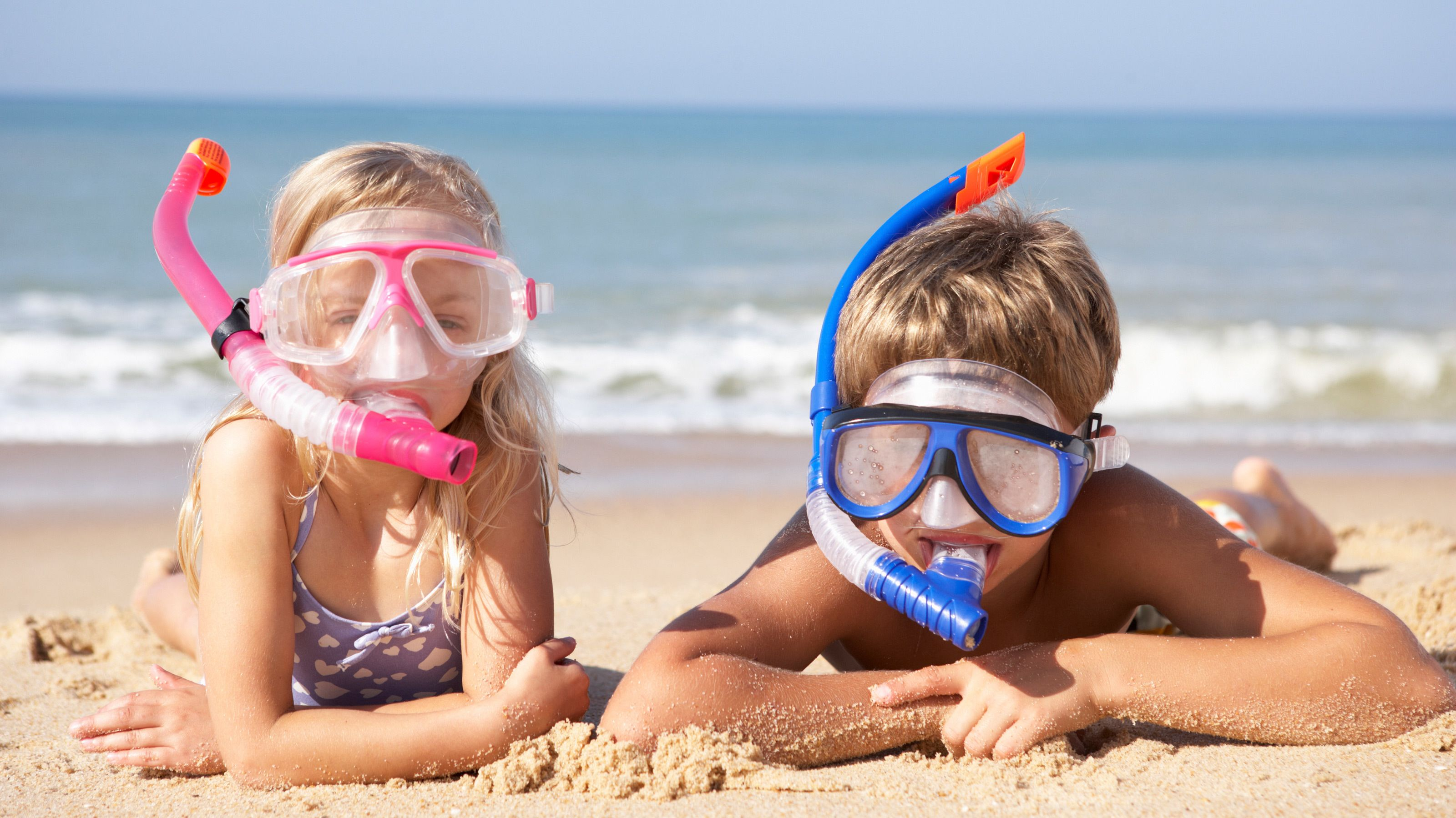 Two kids with snorkel masks on beach