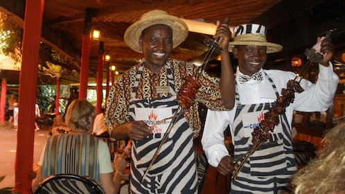 men with meat on skewers in africa