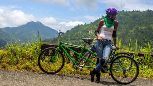 Woman leaning on a bicycle in the blue mountains of jamaica