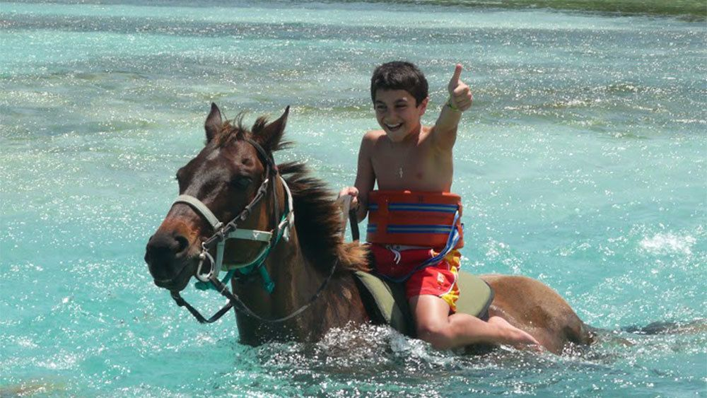 boy horse back swimming in the ocean along the jamaican coast