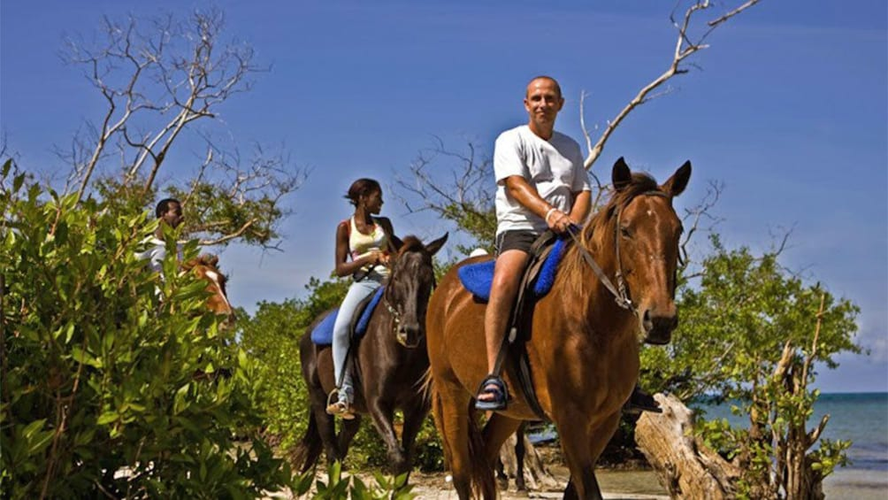 Show item 3 of 7. horse back riders along the beach in jamaica