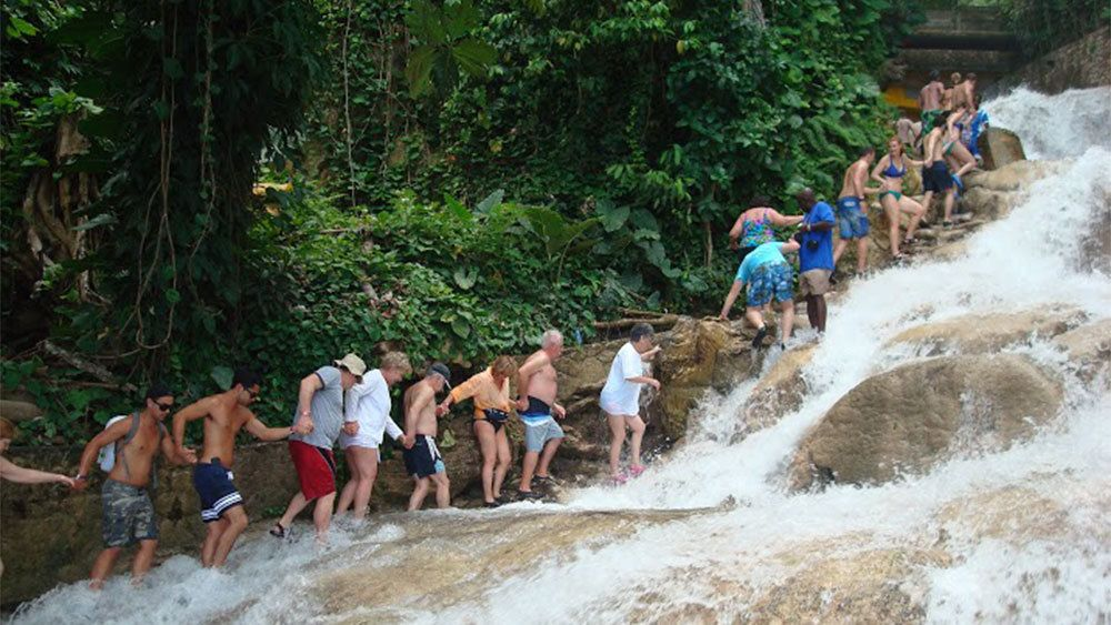 People hiking up a waterfall holding hand in Jamaica