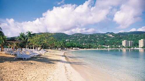 sandy beach with chairs in jamaica