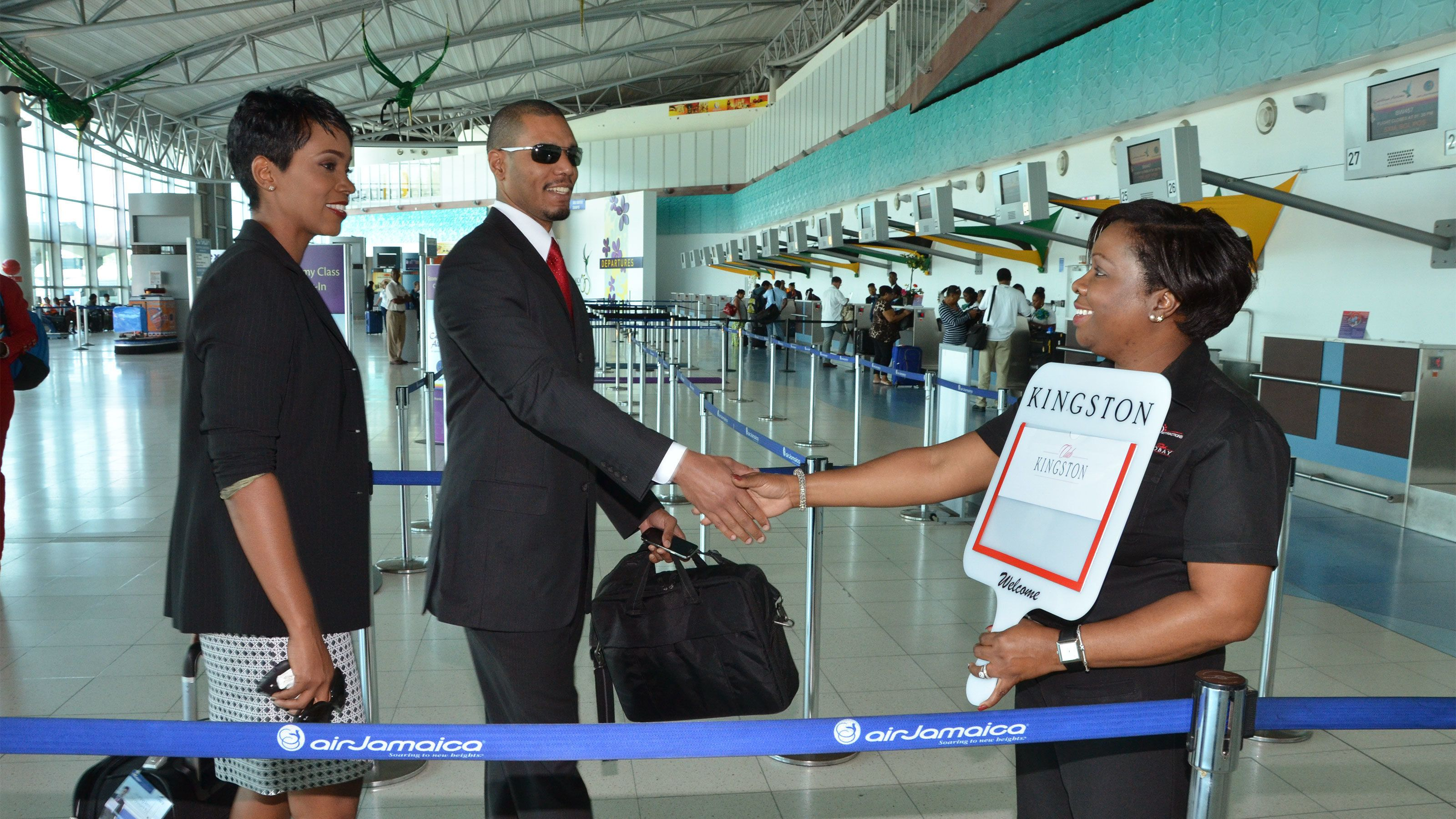travelers getting greeted by a employee of club kingston vip airport lounge in jamaica