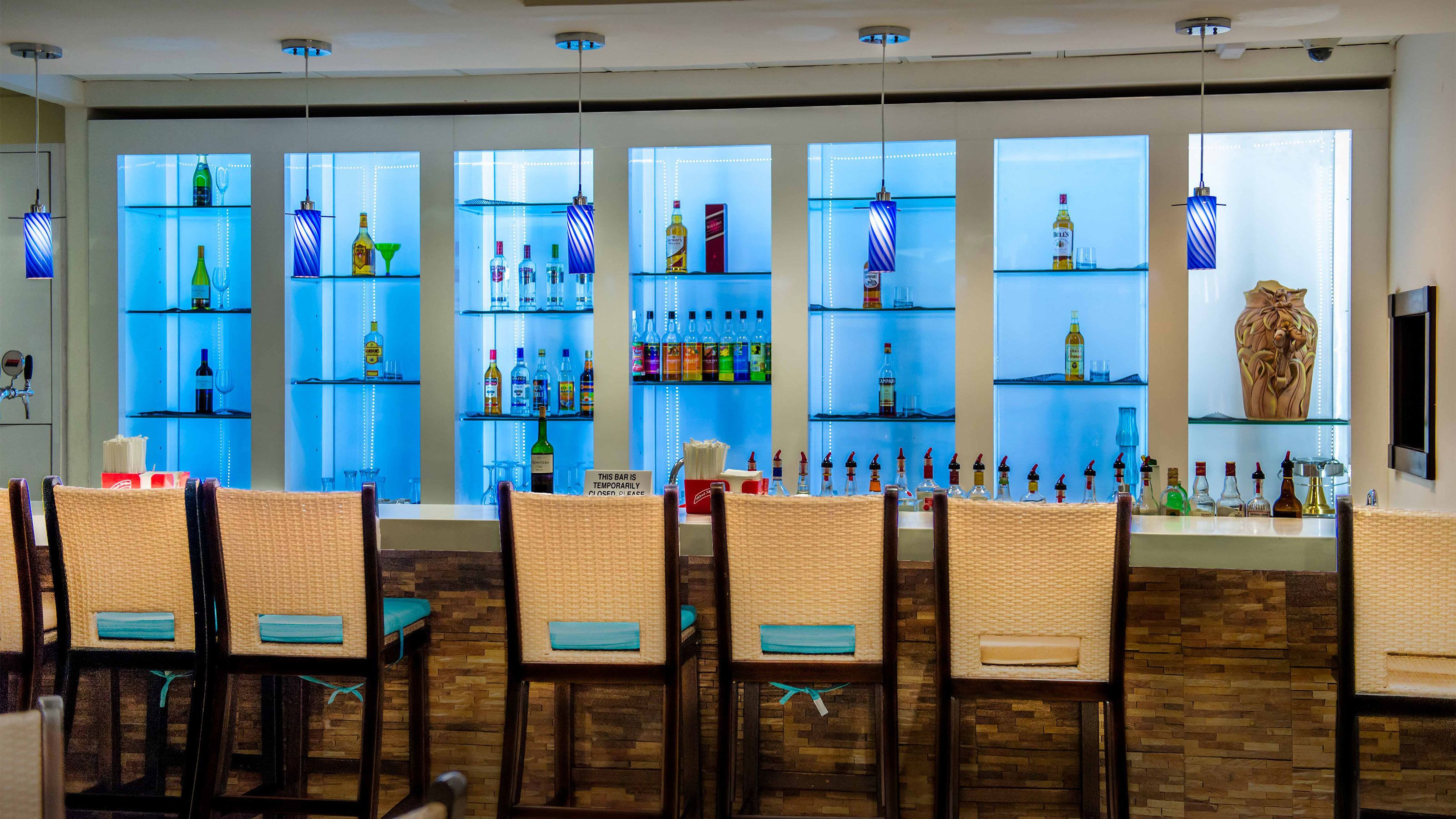Bar with colored lights on shelfs at VIP Mobay Lounge in Jamaica