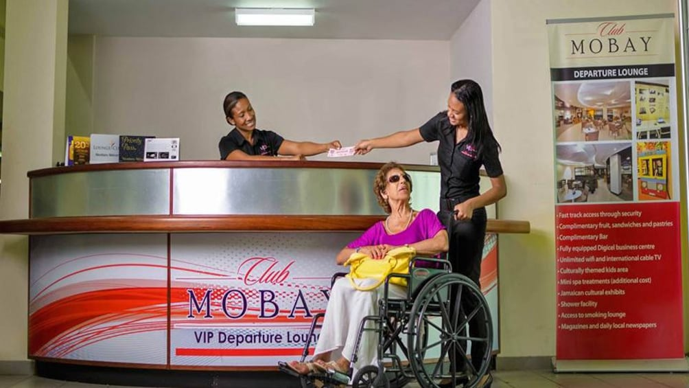 woman helping lady in wheel chair at club mobay