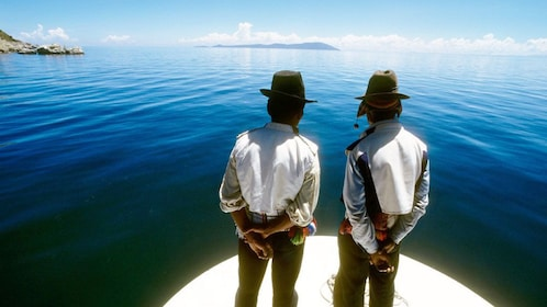 Two Peruvian men standing on a boat On Lake titicaca