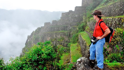A single tourist looks over the fog covered ruins