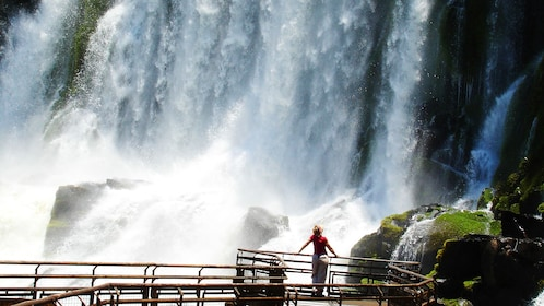 Close view of Iguazu Falls in Argentina with someone standing in awe looking at the falls