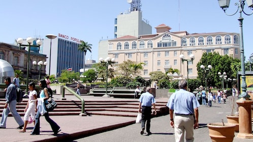 People walking through the square in front of the Gran Hotel in San Jose