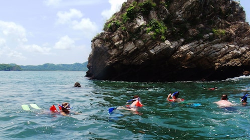 Snorkelers swimming past a large rock formation in the water near Tortuga Island Beach in Costa Rica