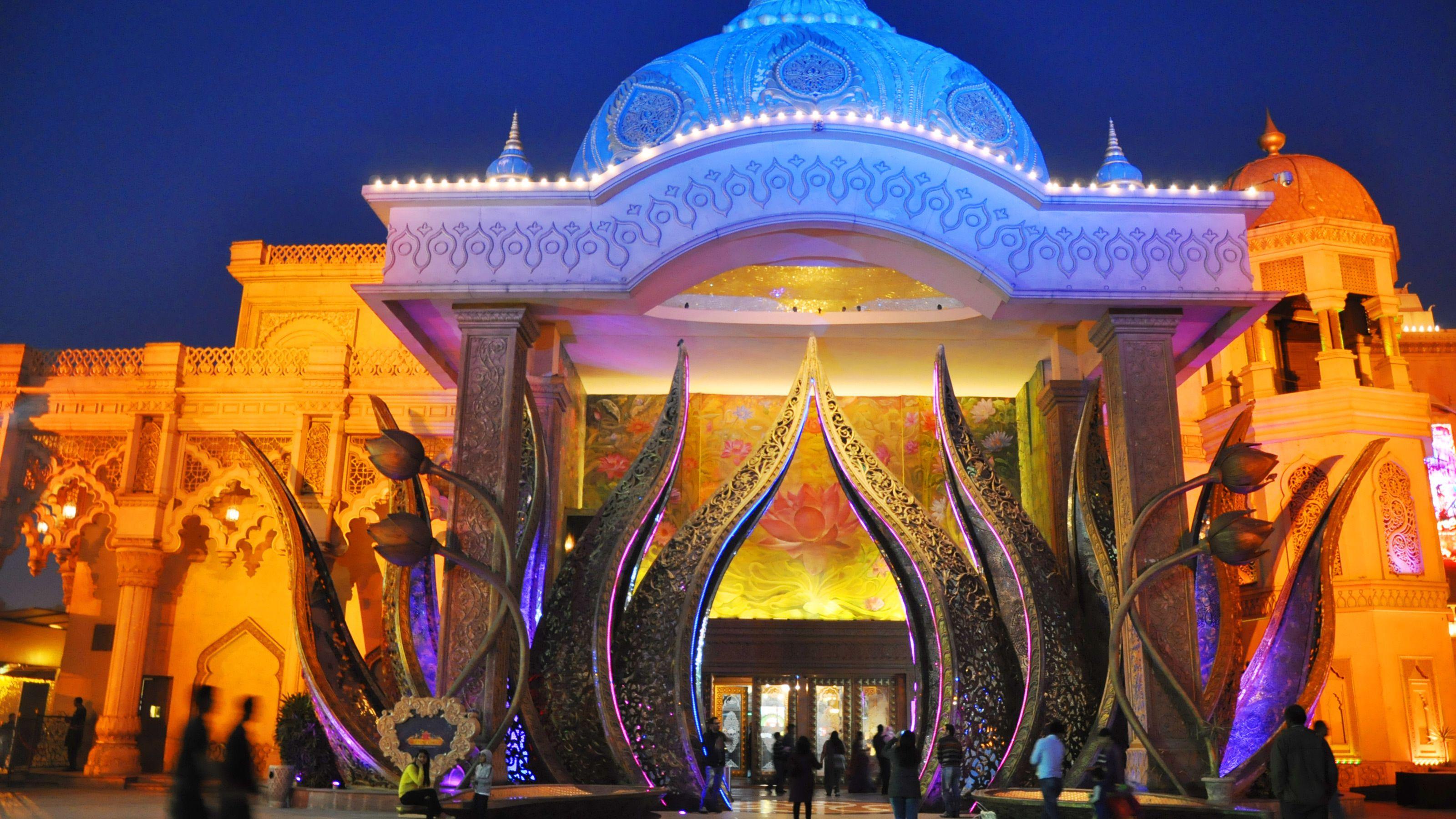 Exterior of the Kingdom of Dreams theater illuminated at night